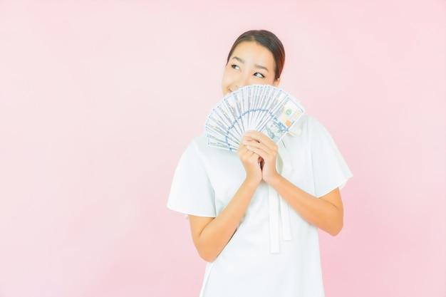Retrato de uma bela jovem asiática com muito dinheiro e muito dinheiro na parede cor de rosa