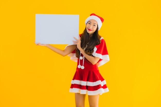 Retrato de uma bela jovem asiática com roupas de natal e chapéu sorrindo com tabuleiro vazio
