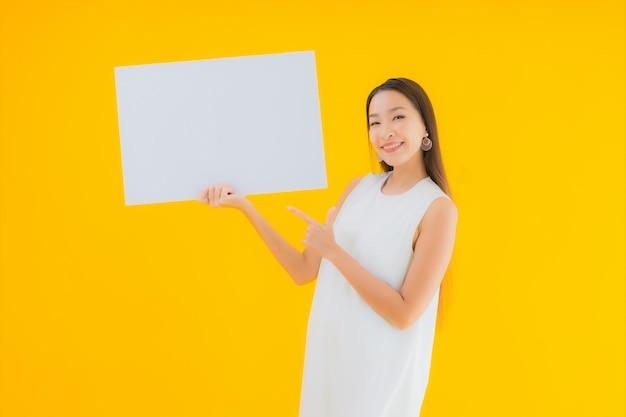 Retrato de uma bela jovem asiática com um cartaz ou cartaz branco vazio