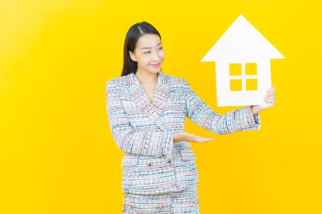 Retrato de uma bela jovem asiática com uma placa de papel de casa ou casa na parede colorida
