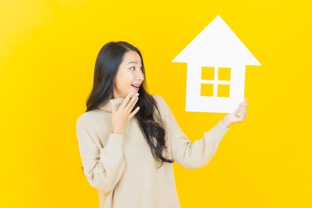 Retrato de uma bela jovem asiática com uma placa de papel na parede amarela.