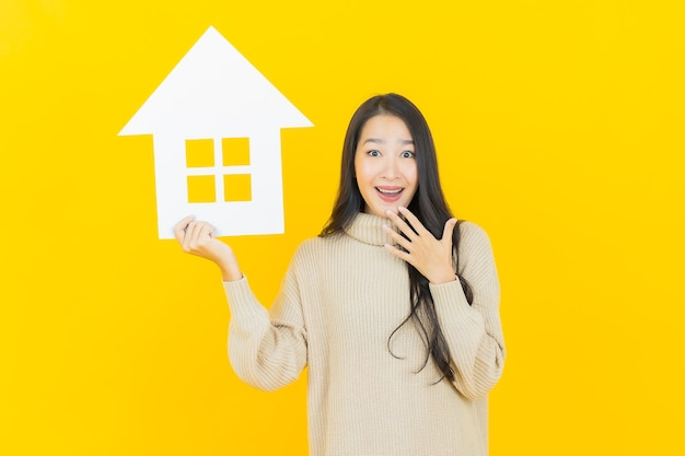 Retrato de uma bela jovem asiática com uma placa de papel para casa ou casa na parede amarela