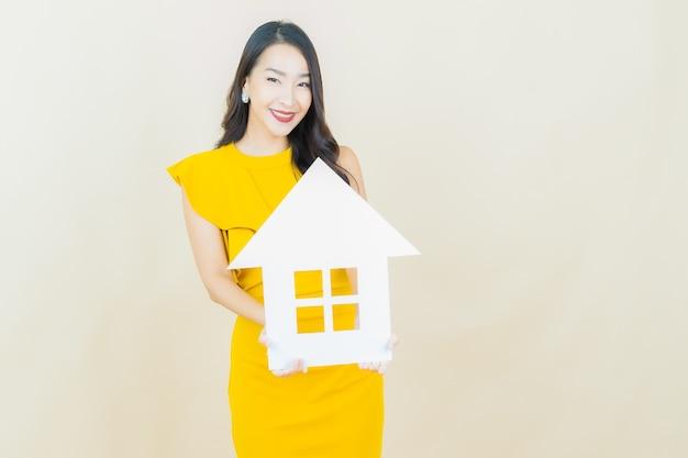 Retrato de uma bela jovem asiática com uma placa de papel para casa ou casa na parede bege