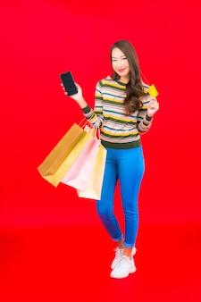 Retrato de uma bela jovem asiática com uma sacola de compras colorida e um cartão de crédito na parede vermelha