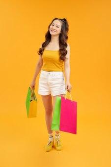 Retrato de uma bela jovem asiática com uma sacola de compras colorida em um fundo amarelo isolado.
