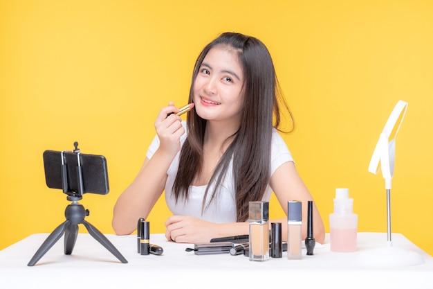 Retrato de uma bela jovem asiática de beleza vlogger fazendo maquiagem olhando para a câmera do blogger gravando e transmitindo vídeo para compartilhar nas redes sociais