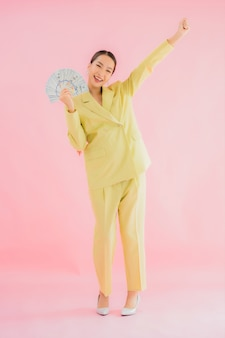 Retrato de uma bela jovem asiática de negócios com muito dinheiro ou dinheiro em cores