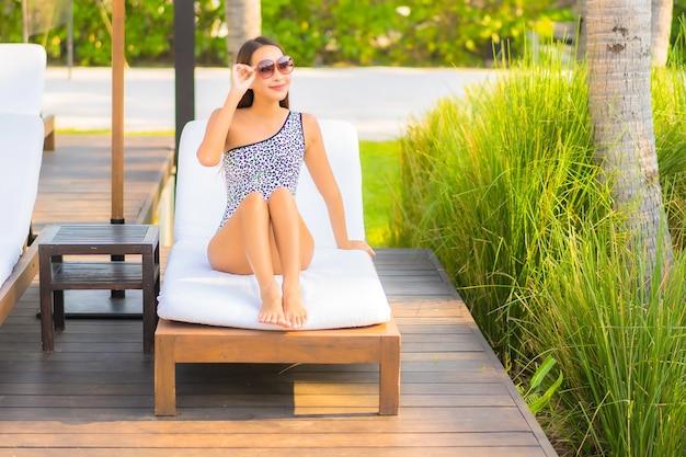 Retrato de uma bela jovem asiática relaxando ao redor da piscina em um hotel resort de férias