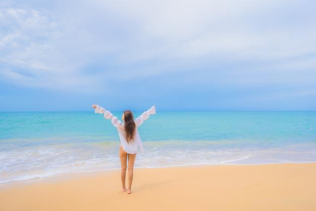 Retrato de uma bela jovem asiática relaxando ao redor da praia, mar, oceano, em viagens de férias