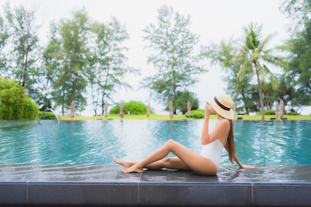 Retrato de uma bela jovem asiática relaxando ao redor de uma piscina em um hotel resort perto do mar