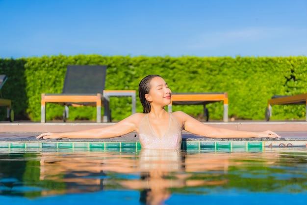Retrato de uma bela jovem asiática relaxando ao redor de uma piscina em um resort de hotel