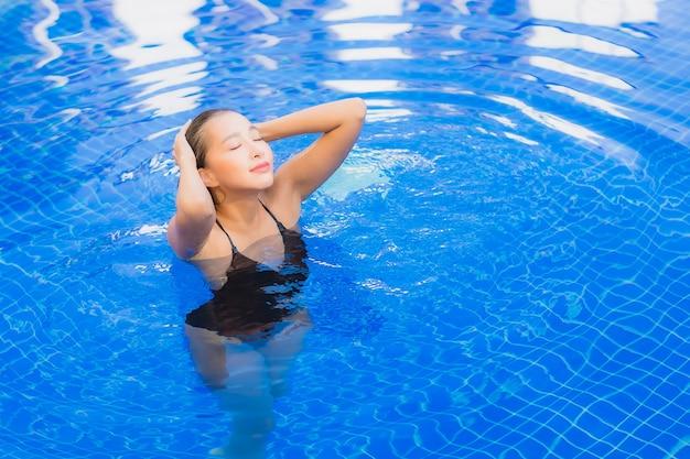 Retrato de uma bela jovem asiática relaxando ao redor de uma piscina em um resort hotel