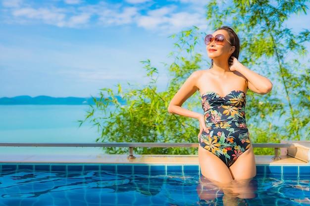 Retrato de uma bela jovem asiática relaxando em uma piscina com vista para o mar