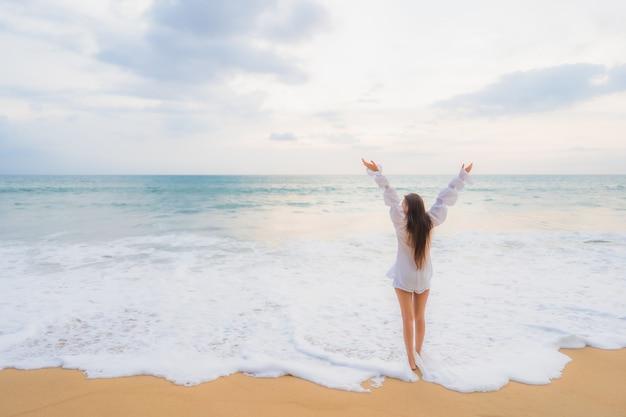 Retrato de uma bela jovem asiática relaxando em uma praia ao ar livre em viagens de férias