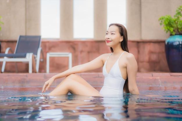 Retrato de uma bela jovem asiática relaxando na piscina Foto gratuita