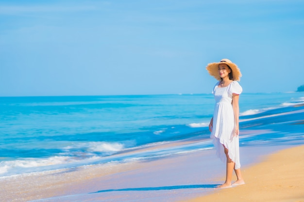 Retrato de uma bela jovem asiática relaxando na praia com nuvens brancas no céu azul em viagens de férias