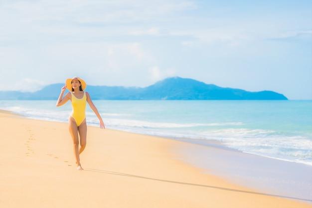 Retrato de uma bela jovem asiática relaxando na praia em viagens de férias
