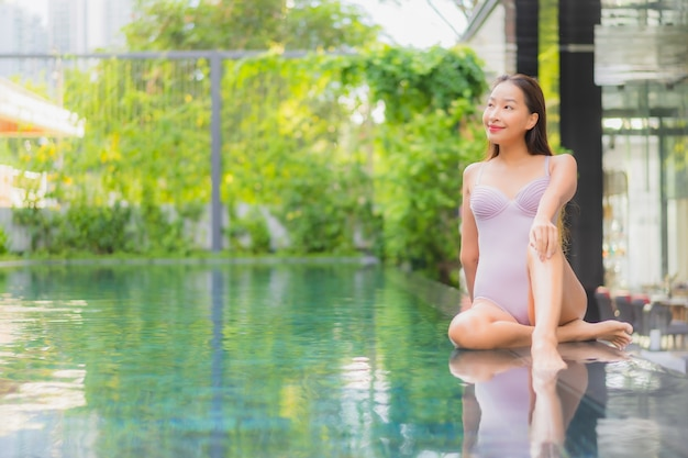Retrato de uma bela jovem asiática relaxando, sorrindo, lazer ao redor de uma piscina externa em um hotel resort