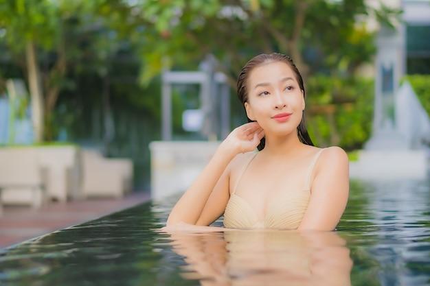 Retrato de uma bela jovem asiática relaxando um sorriso ao redor de uma piscina em um hotel resort em uma viagem de férias