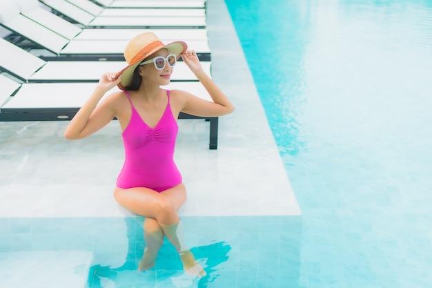 Retrato de uma bela jovem asiática relaxando um sorriso ao redor de uma piscina em um hotel resort