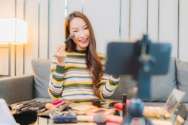 Retrato de uma bela jovem asiática revê e usa cosméticos no sofá