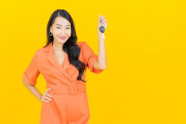 Retrato de uma bela jovem asiática sorrindo com a chave do carro em amarelo