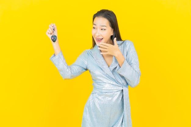 Retrato de uma bela jovem asiática sorrindo com a chave do carro na parede amarela