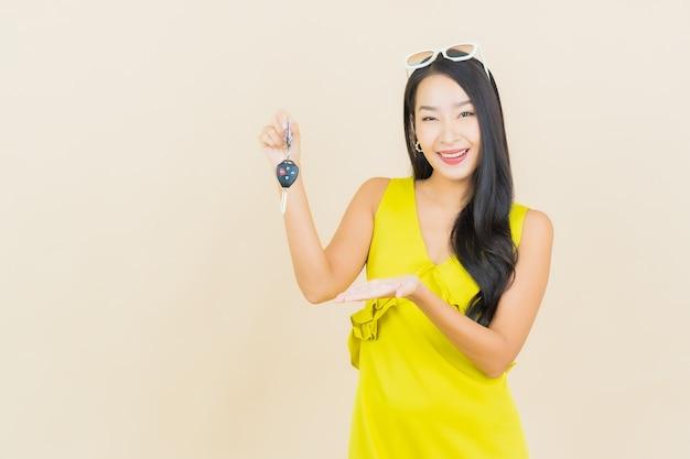 Retrato de uma bela jovem asiática sorrindo com a chave do carro na parede colorida