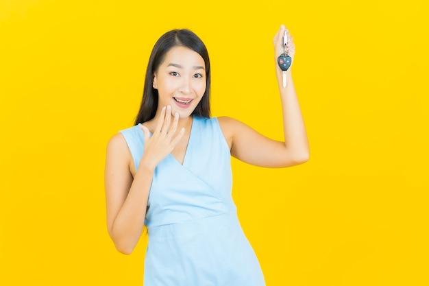 Retrato de uma bela jovem asiática sorrindo com a chave do carro na parede de cor amarela
