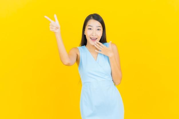Retrato de uma bela jovem asiática sorrindo com ação na parede de cor amarela