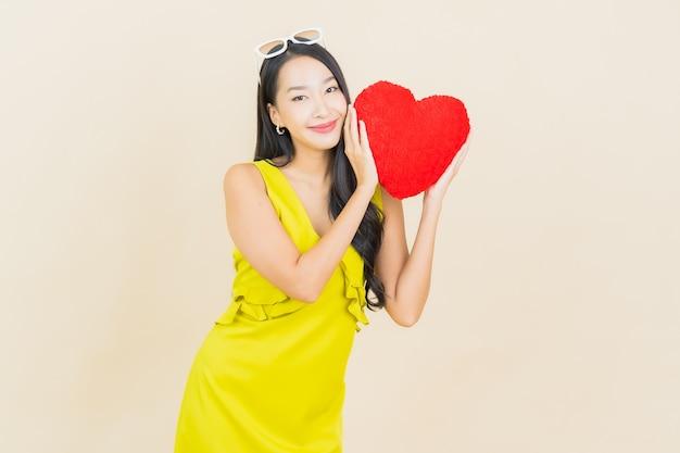 Retrato de uma bela jovem asiática sorrindo com almofada em forma de coração na parede colorida