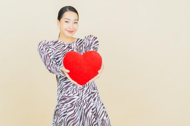 Retrato de uma bela jovem asiática sorrindo com almofada em formato de coração bege