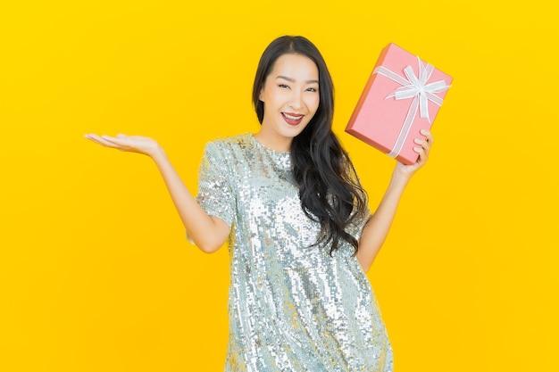 Retrato de uma bela jovem asiática sorrindo com caixa de presente vermelha em amarelo