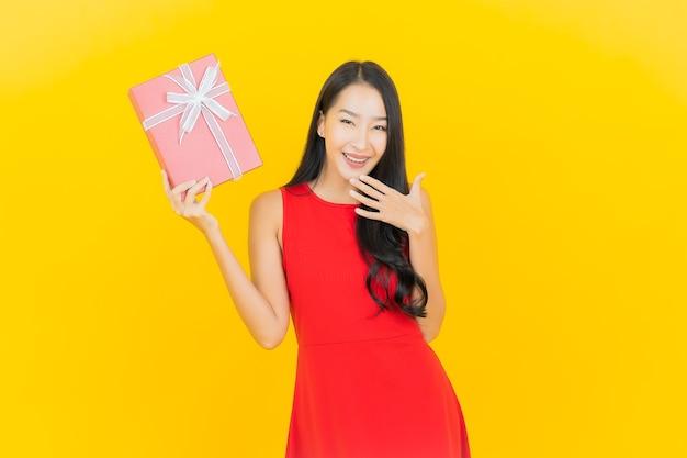 Retrato de uma bela jovem asiática sorrindo com caixa de presente vermelha na parede amarela