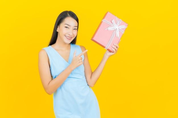 Retrato de uma bela jovem asiática sorrindo com caixa de presente vermelha na parede de cor amarela