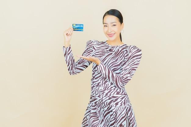 Retrato de uma bela jovem asiática sorrindo com cartão de crédito em bege