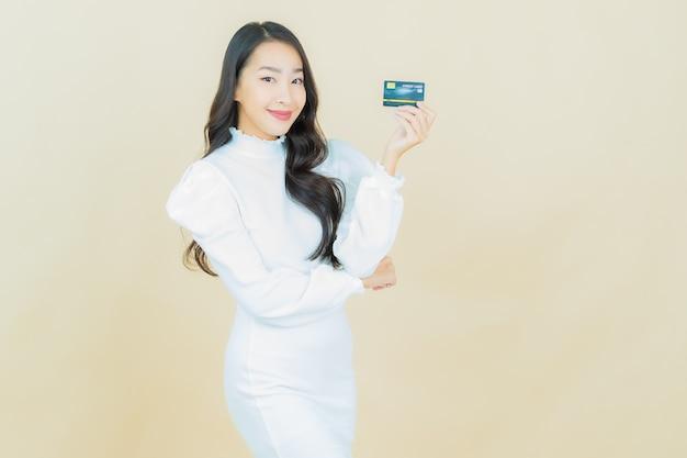 Retrato de uma bela jovem asiática sorrindo com cartão de crédito na parede colorida
