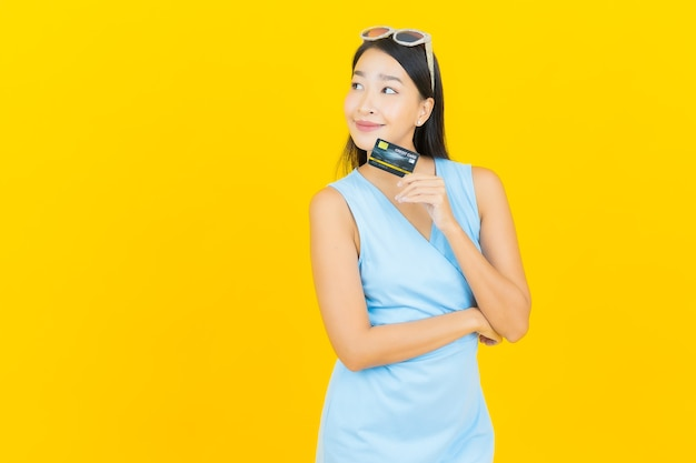 Retrato de uma bela jovem asiática sorrindo com cartão de crédito na parede de cor amarela