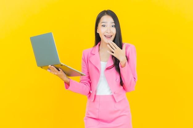 Retrato de uma bela jovem asiática sorrindo com computador laptop na parede amarela isolada
