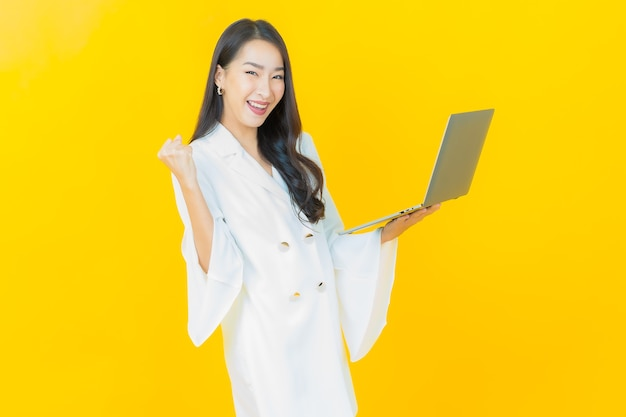 Retrato de uma bela jovem asiática sorrindo com computador laptop na parede amarela
