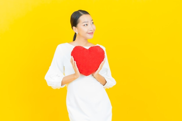 Retrato de uma bela jovem asiática sorrindo com forma de almofada de coração amarelo