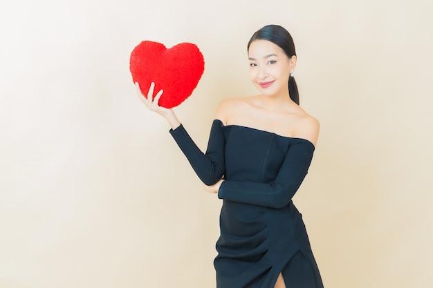 Retrato de uma bela jovem asiática sorrindo com formato de almofada de coração amarelo