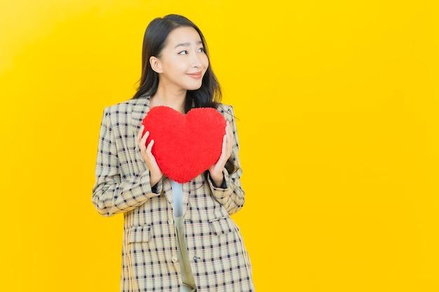 Retrato de uma bela jovem asiática sorrindo com formato de almofada em forma de coração
