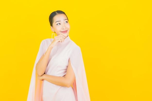 Retrato de uma bela jovem asiática sorrindo com muita ação na parede amarela
