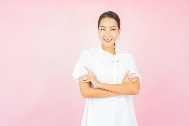 Retrato de uma bela jovem asiática sorrindo com muita ação na parede rosa