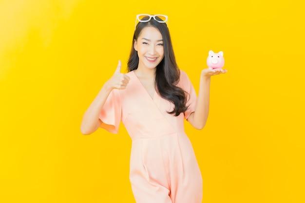 Retrato de uma bela jovem asiática sorrindo com muito dinheiro e dinheiro na parede colorida