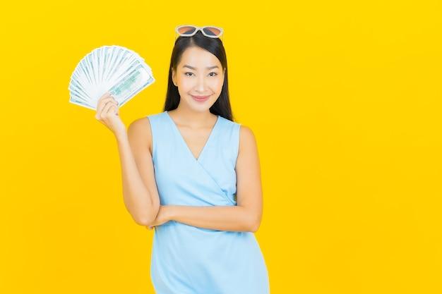 Retrato de uma bela jovem asiática sorrindo com muito dinheiro e dinheiro na parede de cor amarela
