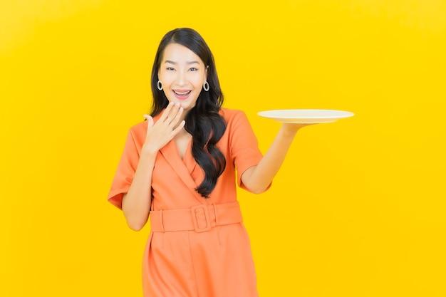 Retrato de uma bela jovem asiática sorrindo com prato vazio em amarelo