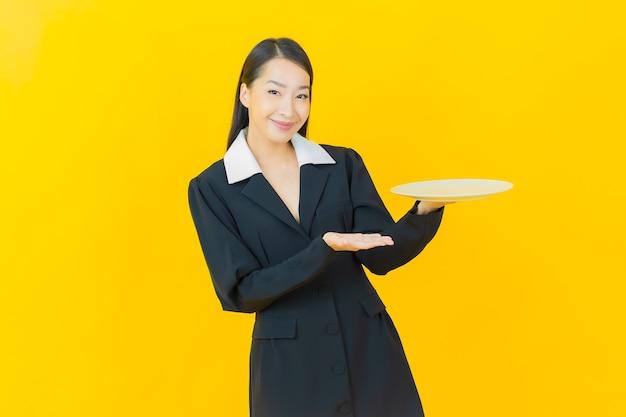 Retrato de uma bela jovem asiática sorrindo com prato vazio na parede colorida