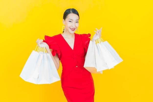 Retrato de uma bela jovem asiática sorrindo com sacolas de compras na parede colorida